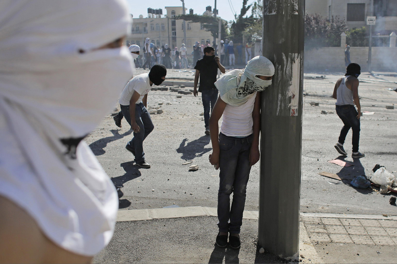 Jul. 3, 2014.  A Palestinian stone-thrower takes cover behind a street pole during clashes with Israeli police in Shuafat, an Arab suburb of Jerusalem.