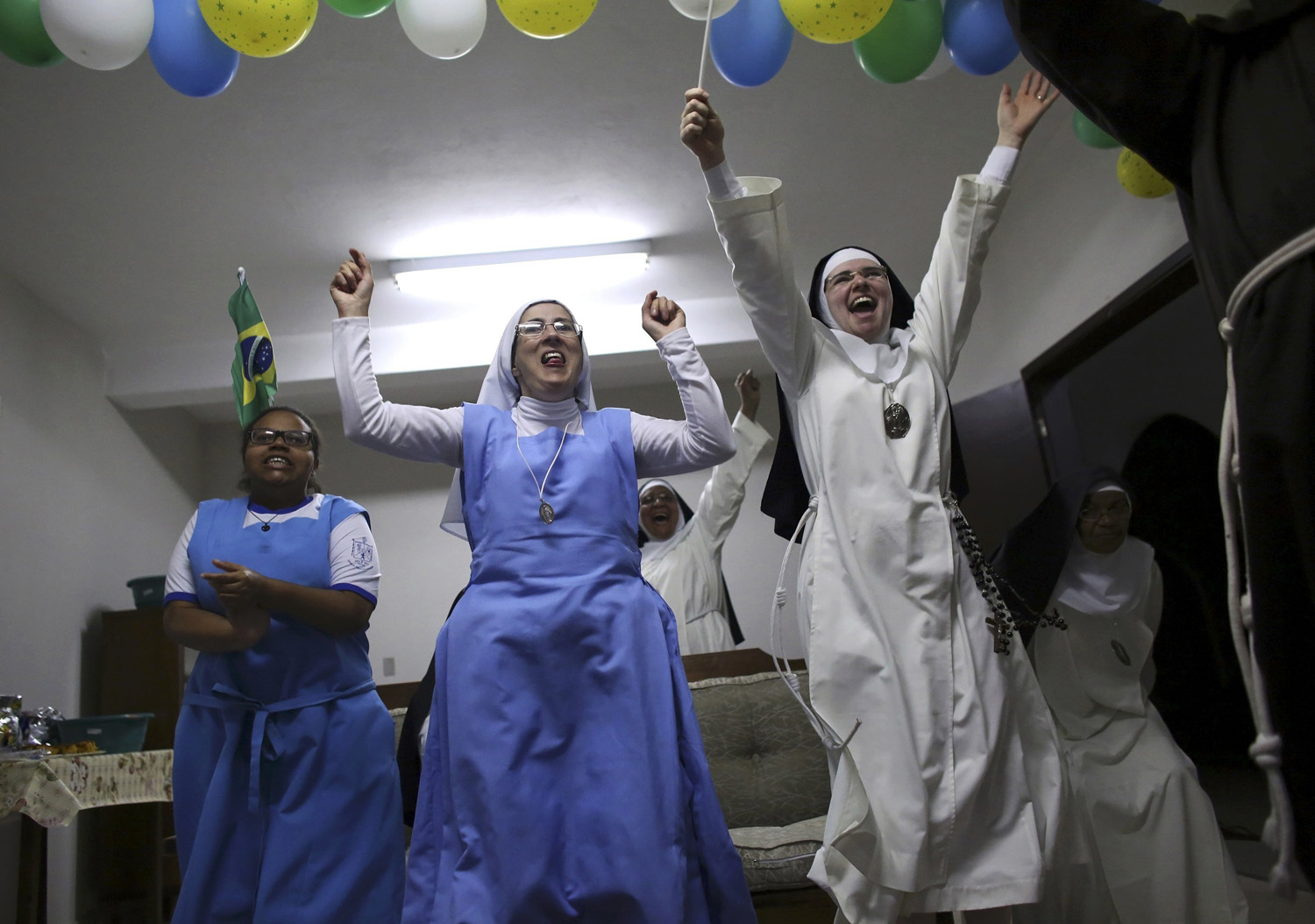 Nuns from the enclosed monastery of Imaculada Conceicao celebrate Brazil's victory as they watch on television at the end of the 2014 World Cup quarter-final soccer match between Brazil and Colombia in Piratininga, Brazil on July 4, 2014.