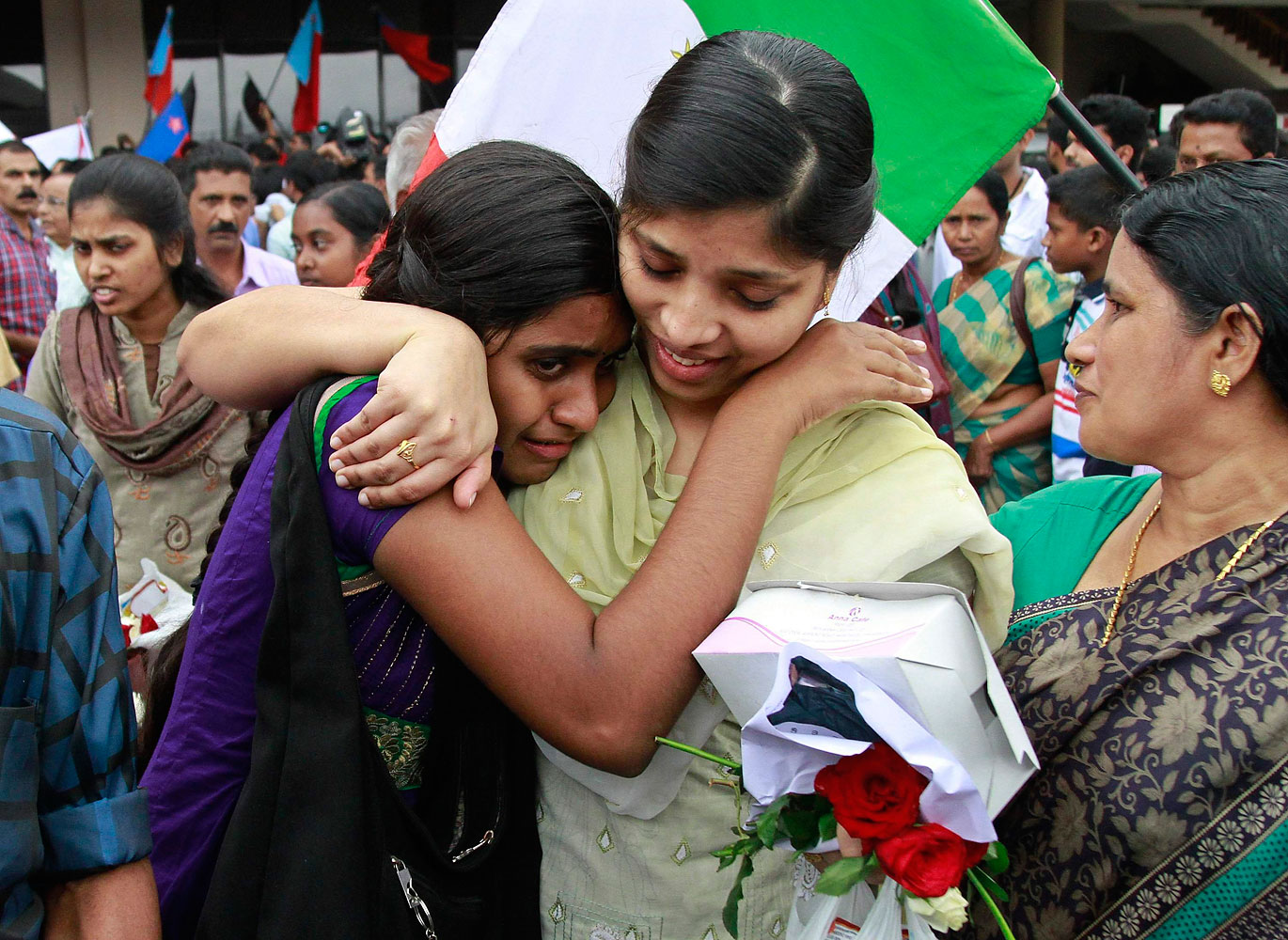 Sherin, center, an Indian nurse caught up in fighting in Iraq, hugs her sister after arriving at the airport in the southern Indian city of Kochi, July 5, 2014.