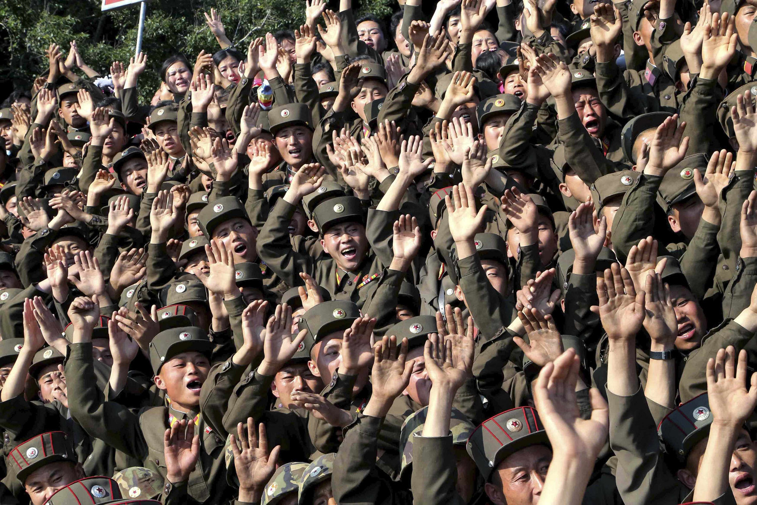 Soldiers wave during a visit by North Korean leader Kim Jong Un to inspect the defence detachment on Ung Islet, which is defending an outpost in the East Sea of Korea, in this undated photo released by North Korea's Korean Central News Agency (KCNA) in Pyongyang July 7, 2014.