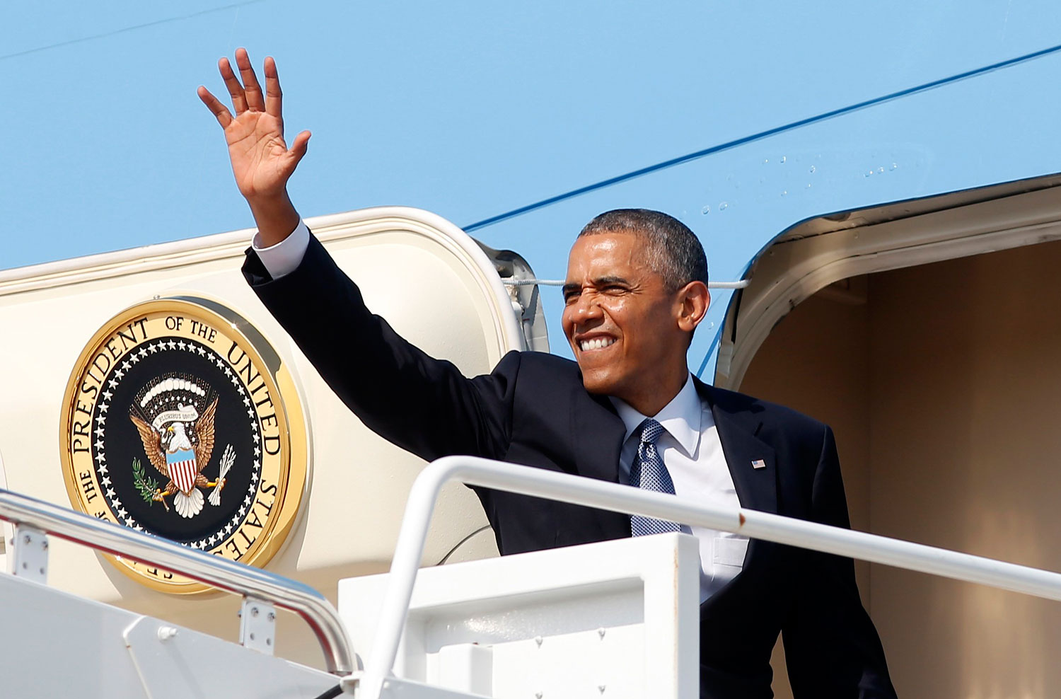 President Barack Obama waves from Air Force One as he departs Joint Base Andrews in Washington en route to Denver July 8, 2014. Obama will then travel to Texas on Wednesday and will meet Governor Rick Perry.