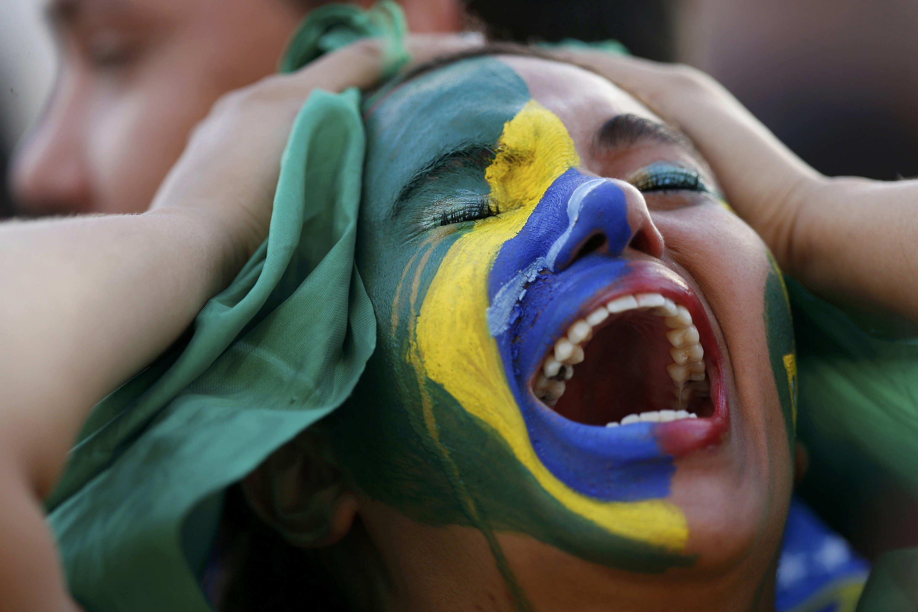 Fans of Brazil react while watching a broadcast of the 2014 World Cup semi-final against Germany at the Fan Fest in Brasilia, Brazil on July 8, 2014.