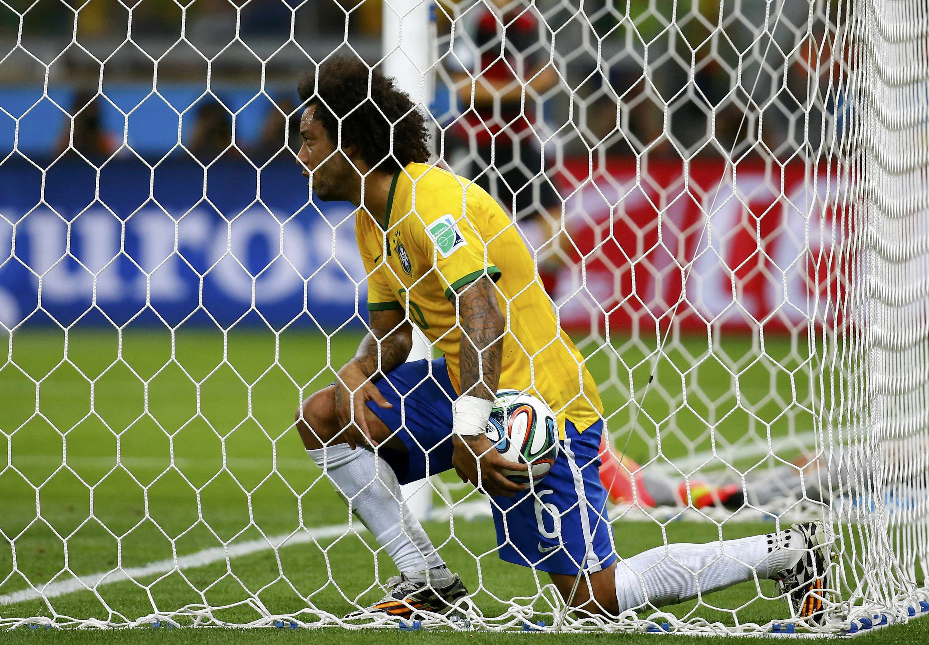 Brazil's Marcelo reacts after Germany's Andre Schuerrle scored the team's seventh goal at the Mineirao stadium in Belo Horizonte on July 8, 2014.