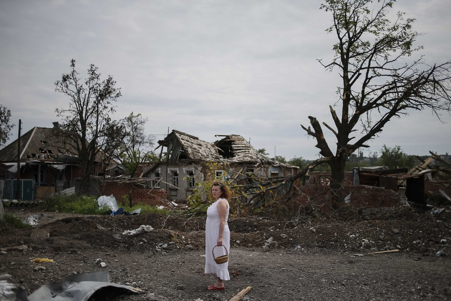 Jul. 9, 2014. A local resident stands outside buildings damaged by a recent shelling in the eastern Ukrainian village of Semenovka.