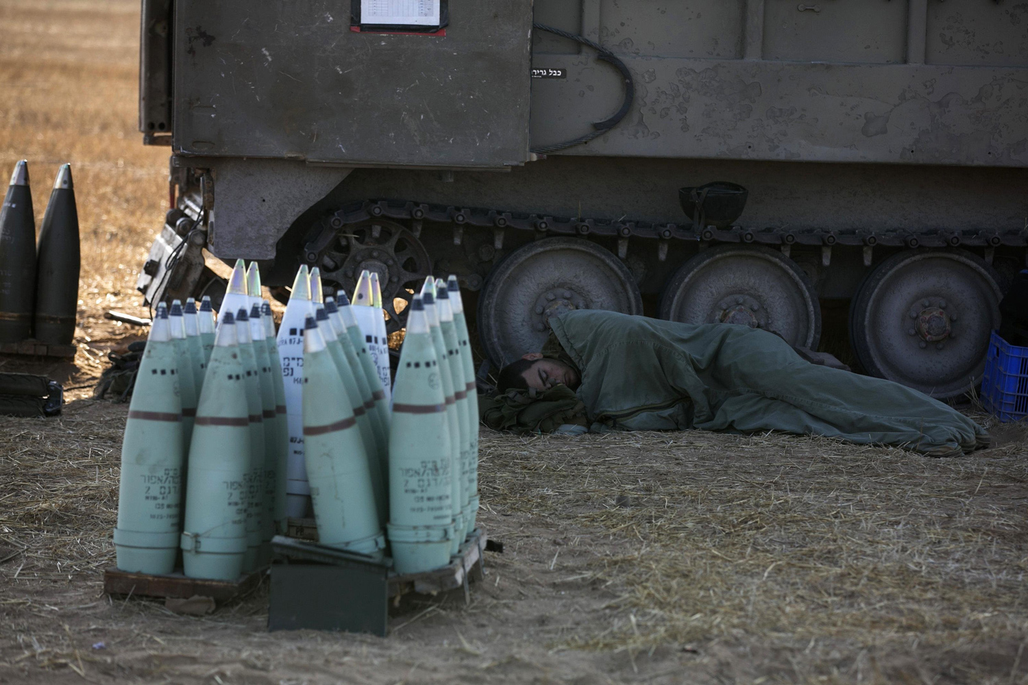 Jul. 10, 2014. An Israeli soldier sleeps next to a mobile artillery unit outside the central Gaza Strip.