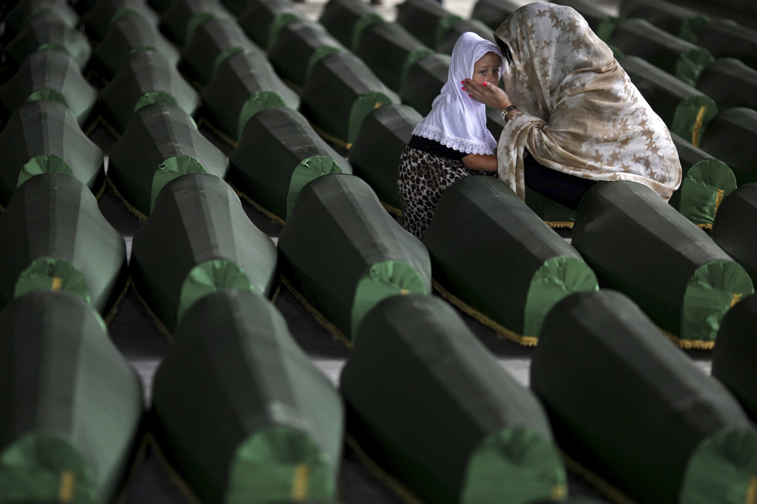 Jul. 10, 2014. A Bosnian Muslim woman and child cry near the coffin of their relative, which is one of the 175 coffins of newly identified victims from the 1995 Srebrenica massacre, in the Potocari Memorial Center, near Srebrenica.
