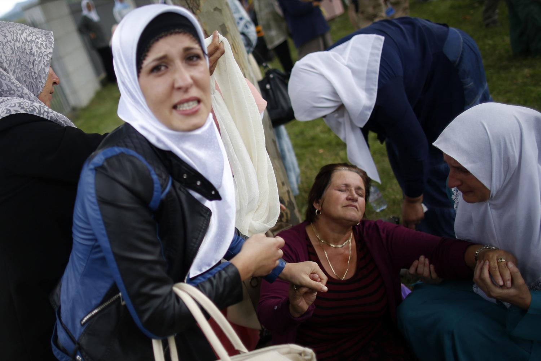 Jul. 10, 2014. A Bosnian Muslim (C) woman reacts near where 175 coffins of newly identified victims from the 1995 Srebrenica massacre are placed, in Potocari Memorial Center, near Srebrenica.