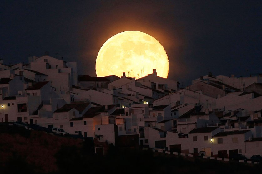 The Supermoon rises over houses in Olvera