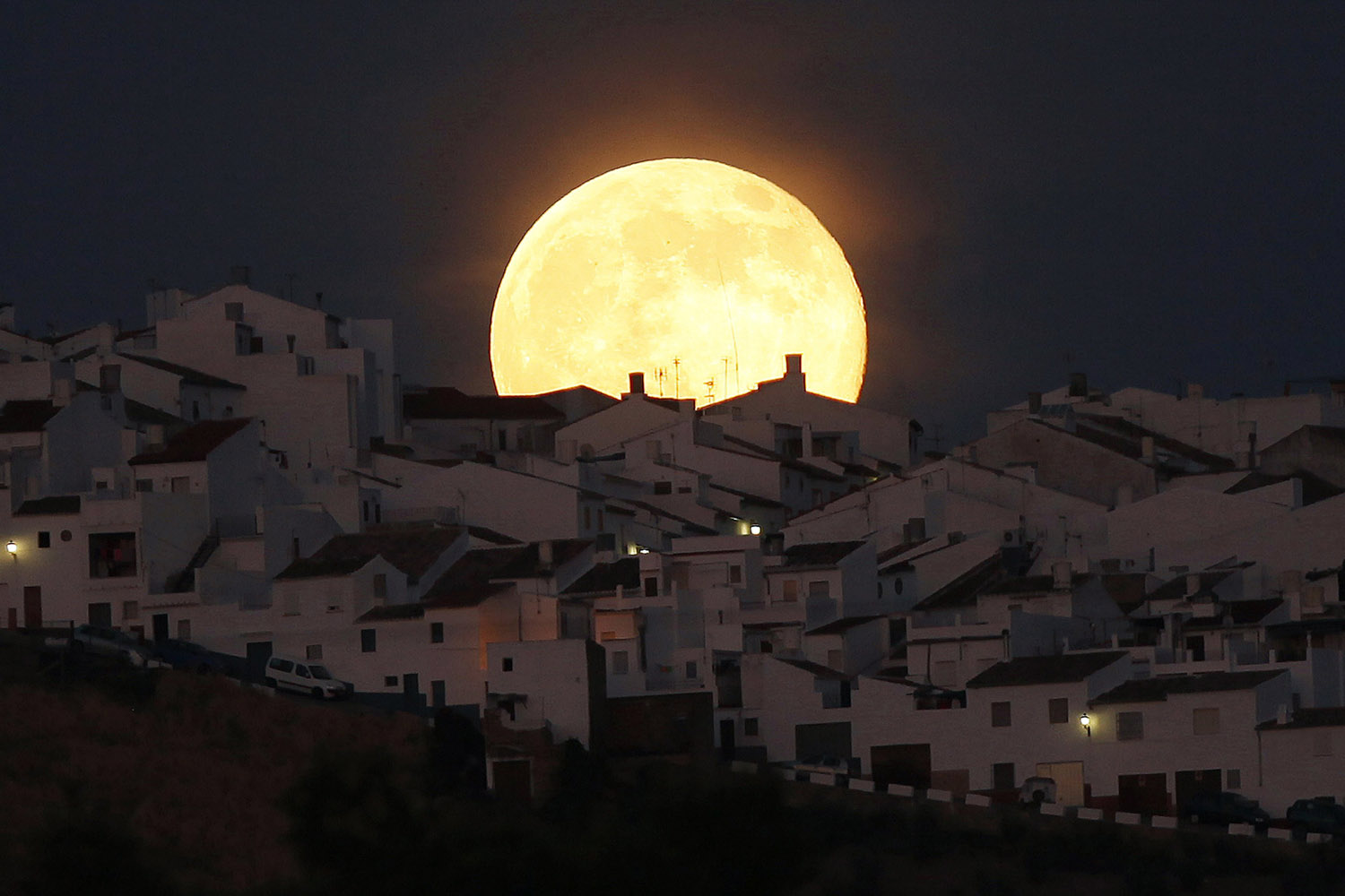 Jul. 12, 2014. The Supermoon rises over houses in Olvera, in the southern Spanish province of Cadiz. Occurring when a full moon or new moon coincides with the closest approach the moon makes to the Earth, the Supermoon results in a larger-than-usual appearance of the lunar disk.