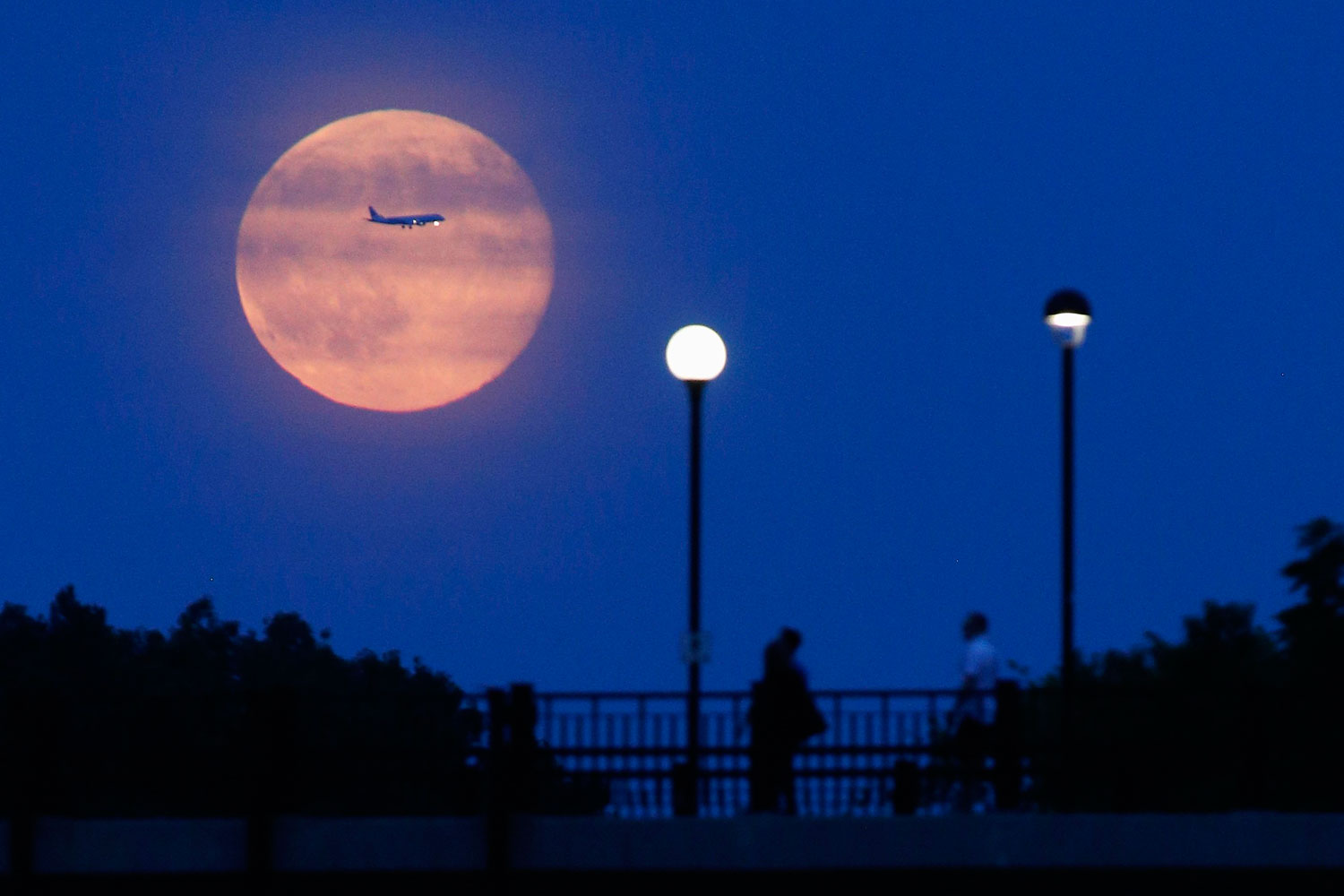Aircraft passes in front of a Supermoon rising over the Rideau Canal in Ottawa July 12, 2014.