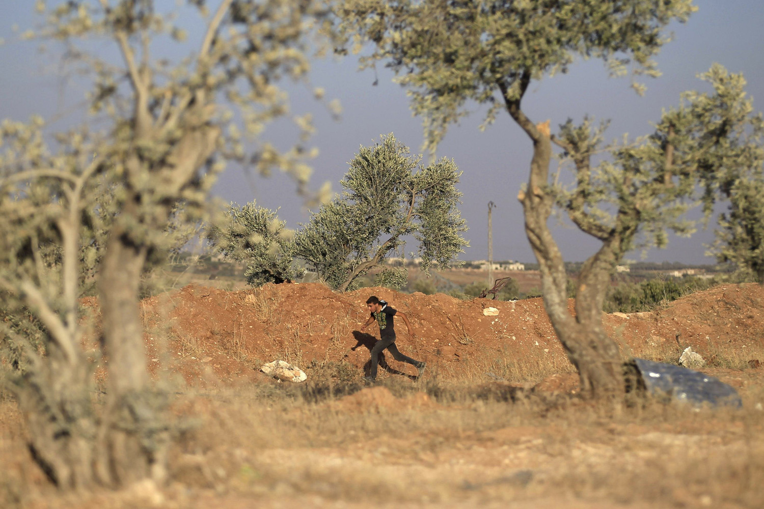 Jul. 14, 2014. A Free Syrian Army fighter runs to avoid snipers loyal to Syria's President Bashar al-Assad in the southern Idlib countryside, Syria.