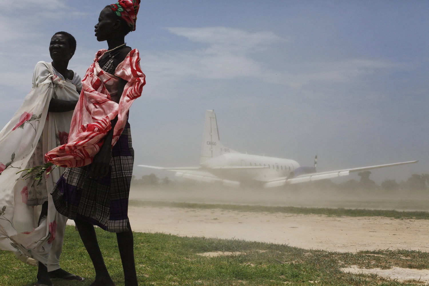 Jul. 15, 2014.                               Women try to avoid dust as a plane, carrying nutrition supplements brought in by Medecins Sans Frontieres (MSF), lands in Leer, South Sudan.