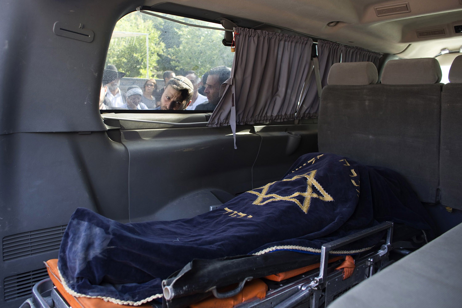 Jul. 16, 2014. An Israeli looks through the window of a van carrying the body of Dror Khenin before his funeral in Yehud, east of Tel Aviv, after Khenin was killed on Tuesday when a short-range rocket landed near the border with Gaza.