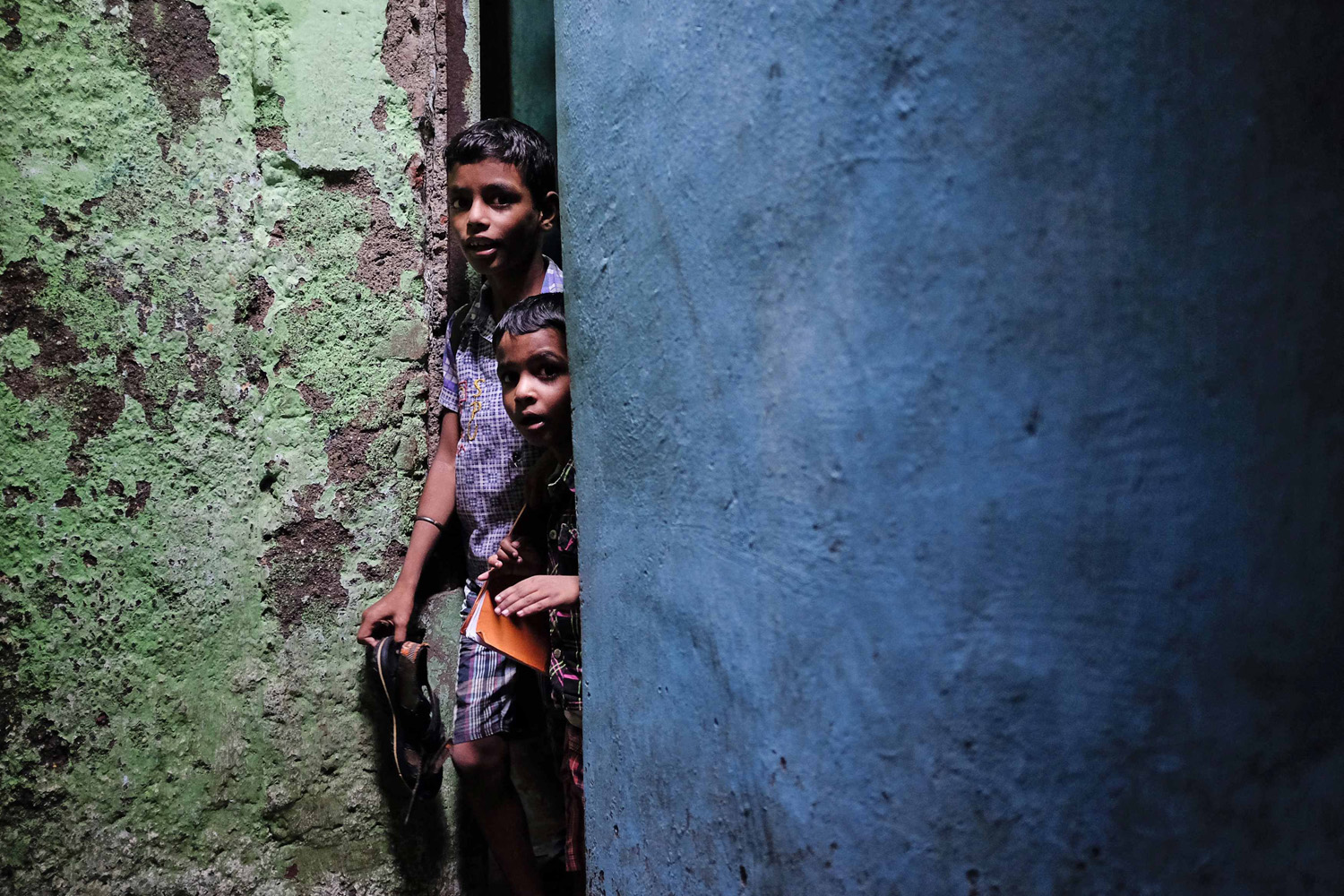Jul. 16, 2014. Schoolchildren walk through an alley after attending private tuition at a slum in Mumbai, India.