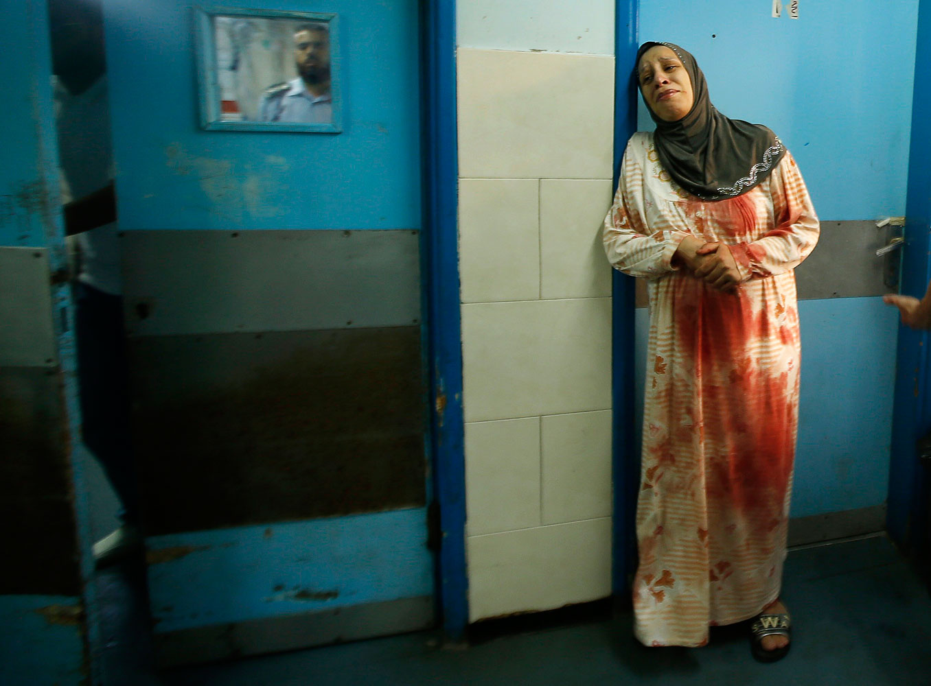 A Palestinian woman wearing clothes stained with the blood of other relatives, who medics said were wounded in Israeli shelling, cries at a hospital in Gaza City July 20, 2014.