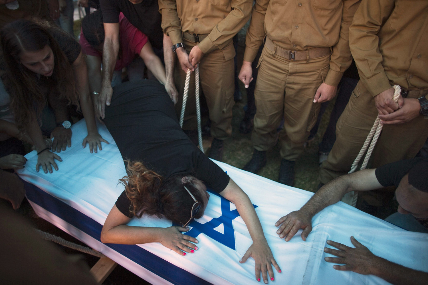 Jul. 22, 2014. The mother of Israeli soldier Tal Yifrah mourns over his flag-covered coffin during his funeral in Rishon Lezion near Tel Aviv.