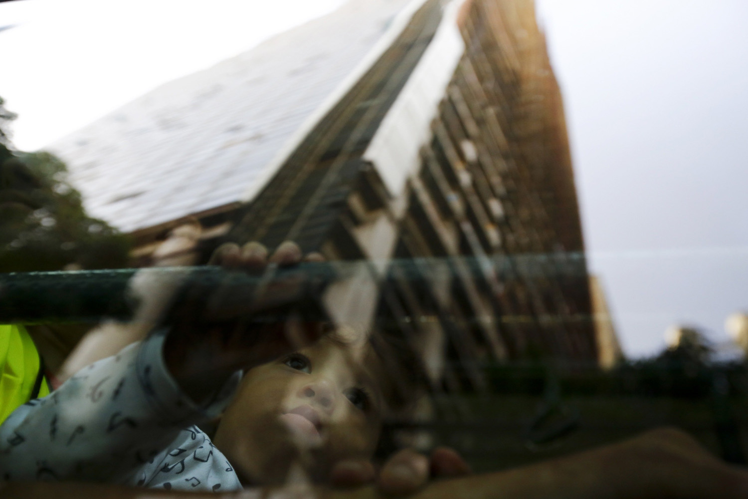 Jul. 22, 2014. An evicted resident of Tower of David sits in a bus, as the building is reflected on the window, which will transport them to the new home in Caracas, Venezuela.