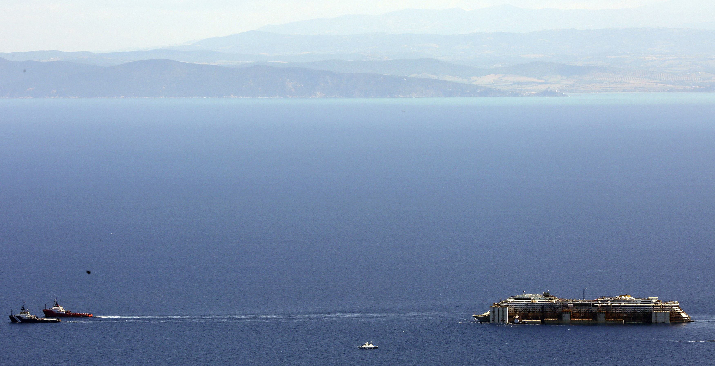 Jul. 23, 2014. Tugboats drag cruise liner Costa Concordia after leaving Giglio Island.