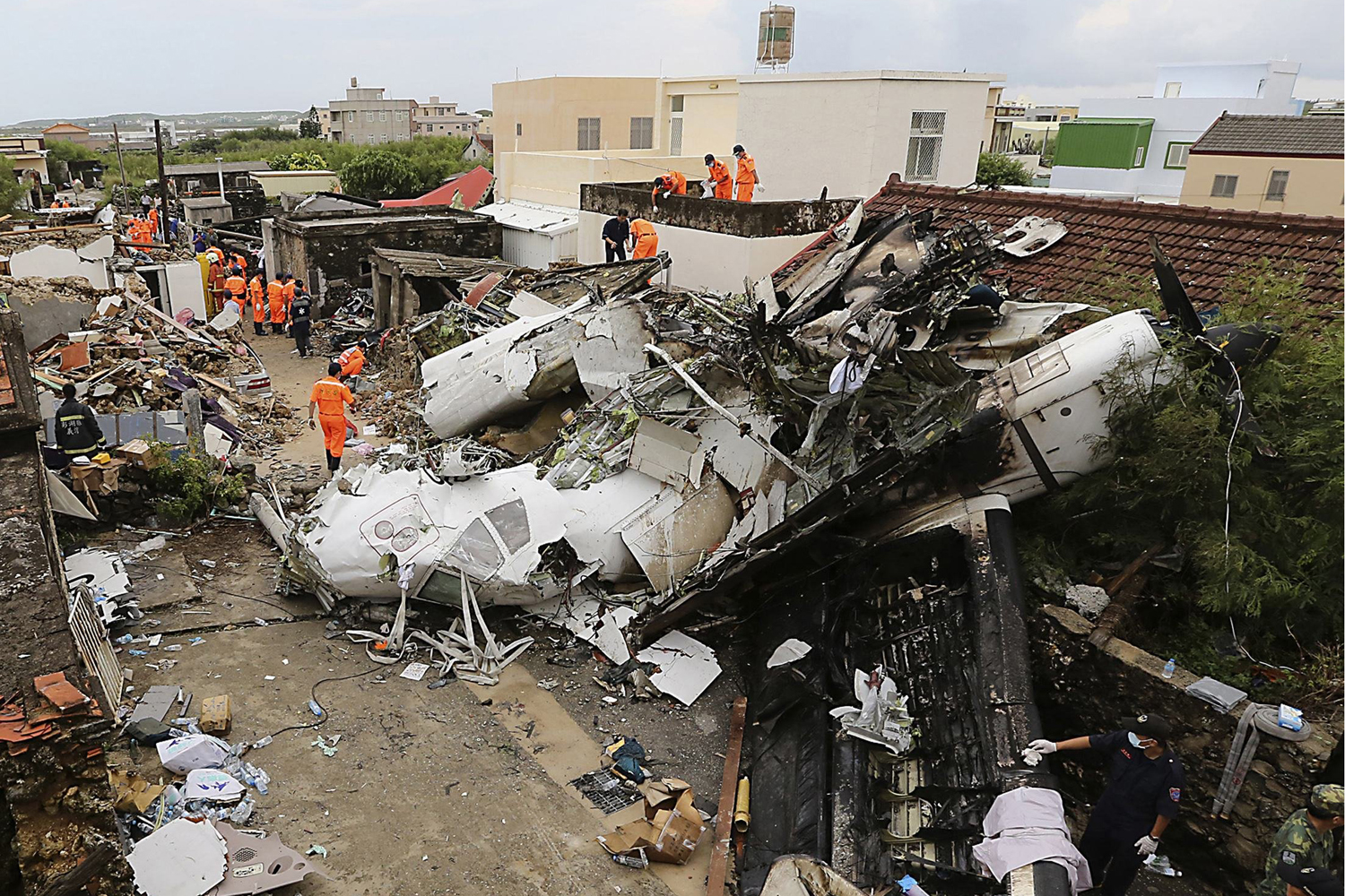 Jul. 24, 2014. Rescue personnel survey the wreckage of a TransAsia Airways turboprop plane that crashed, on Taiwan's offshore island Penghu.