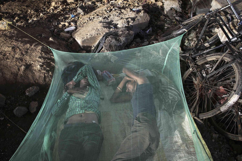 Jul. 24, 2014. Migrant workers sleep under a mosquito net beneath an overpass in Mumbai.