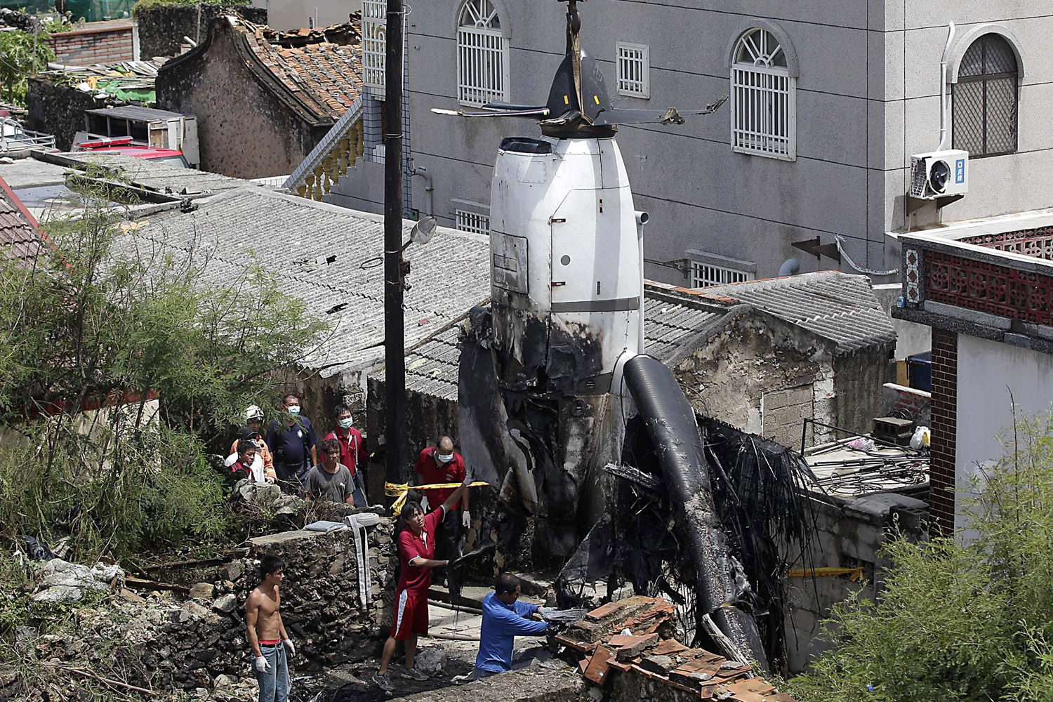 Jul. 25, 2014. Workers remove the wreckage of a TransAsia Airways turboprop plane that crashed on Taiwan's offshore island Penghu.