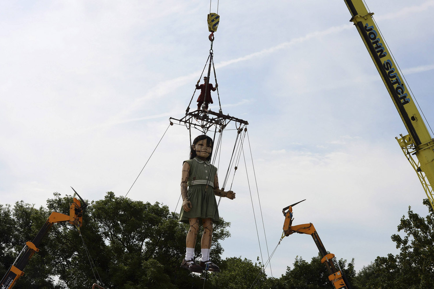 Jul. 26, 2014. A crane lifts a puppet of a girl in Liverpool, northern England. The puppet is part of the  Memories of August 1914  World War One commemorative event in Liverpool.