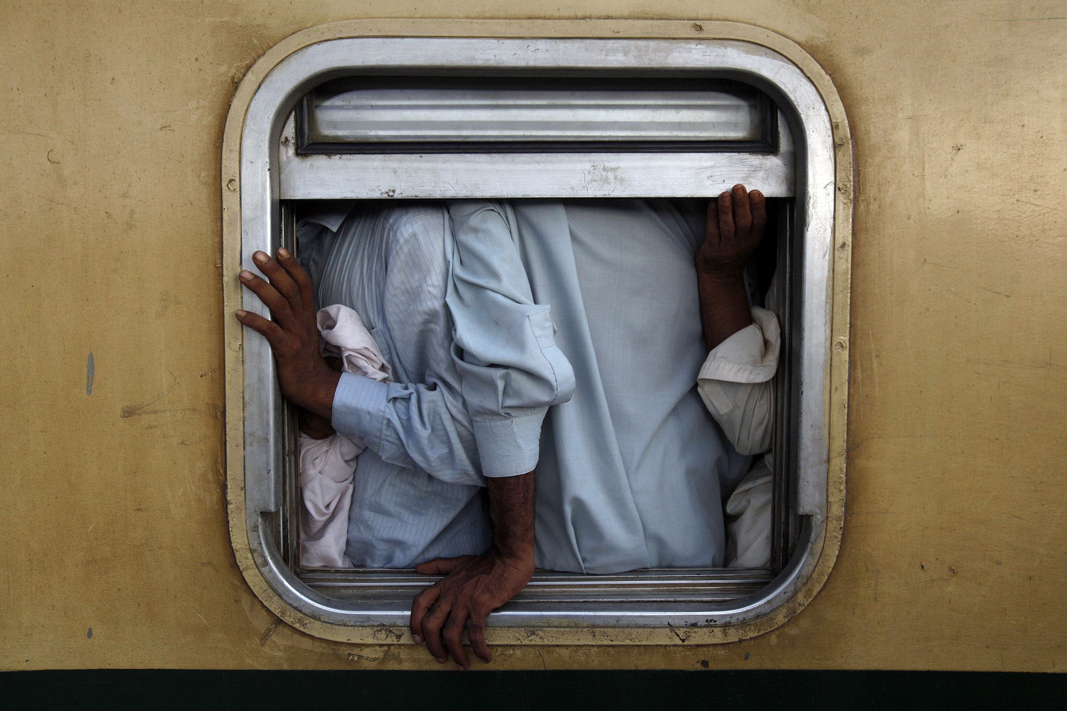 Jul. 27, 2014. Men are seen at the window of a train as they make their way home, ahead of the Eid al-Fitr festival, at Karachi's Cantonment railway station.