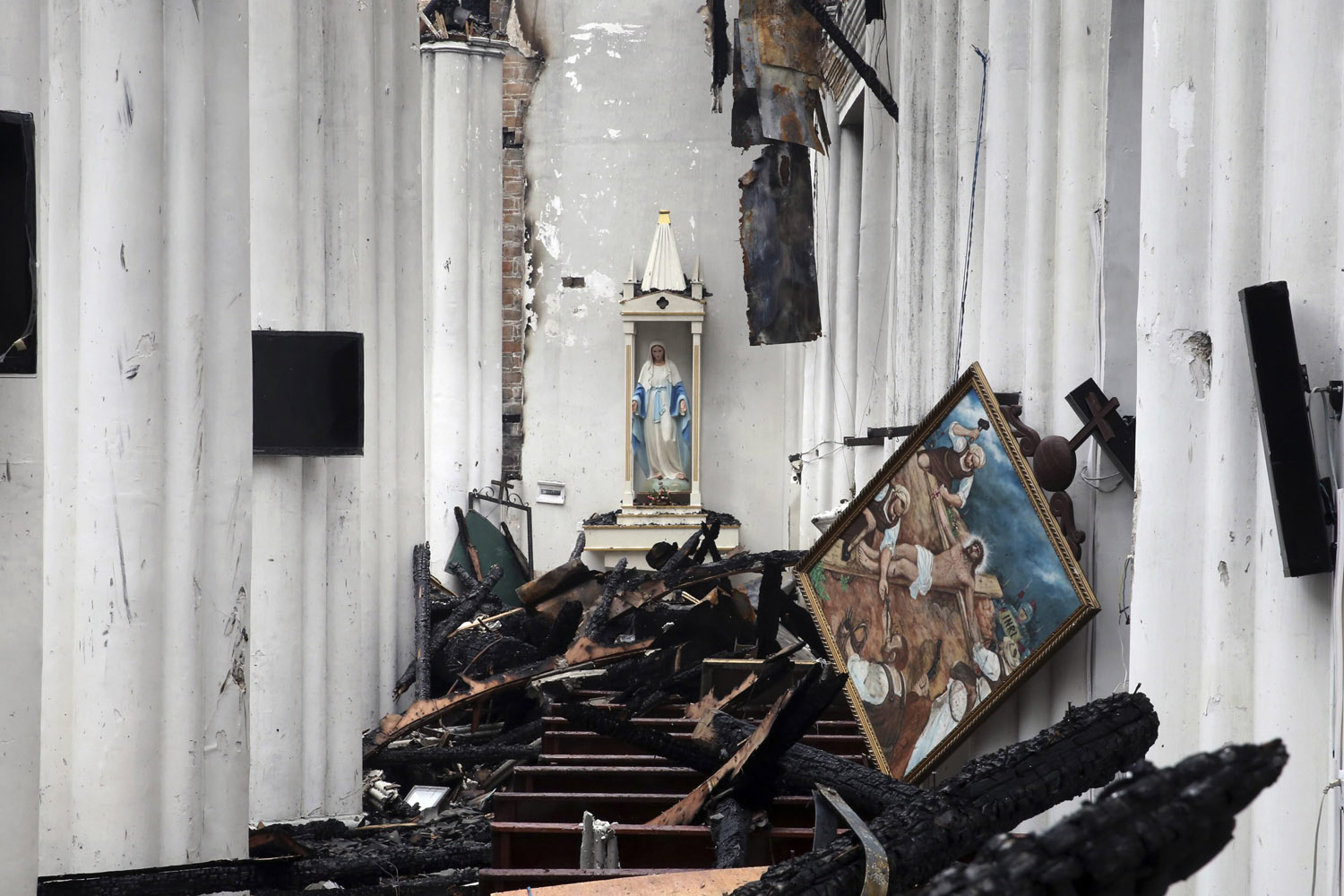 Jul. 28, 2014. A sculpture (C) and a painting are seen above debris after a fire at the Jiangbei Cathedral in Ningbo, Zhejiang province.