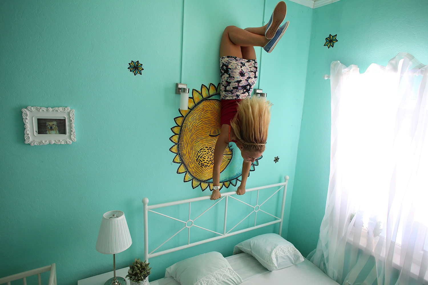 A visitor poses in an upside-down house, in St.Petersburg, Russia, where the floor becomes  the ceiling and furniture appears to defy gravity,  July 25, 2014.