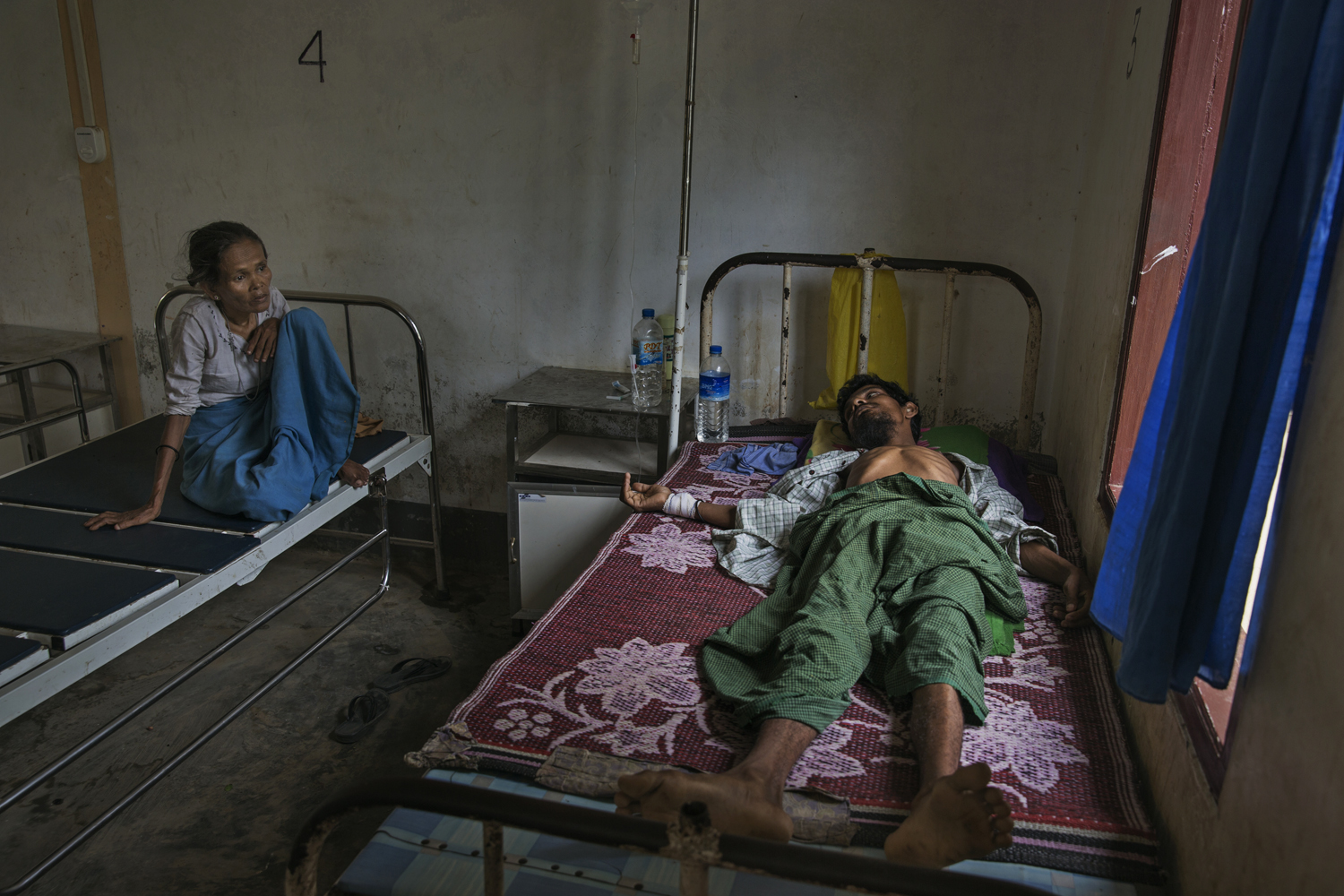 At a government-run hospital in Da Paing, a mother watches over her 45-year-old son Abdul Salam, who suffers from diabetes.