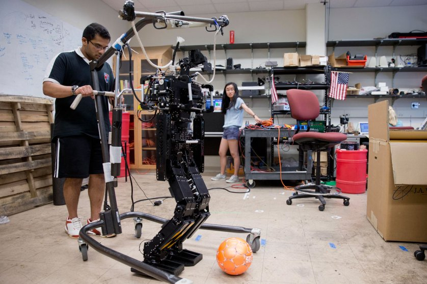 Research associates Larry Vadakedathu, left, and Qin He work with one of their RoboCup entries, a 5-foot-tall metal humanoid named THOR (Tactical Hazardous Operations Robot), in the adult-size league at the University of Pennsylvania in Philadelphia on July 7, 2014.