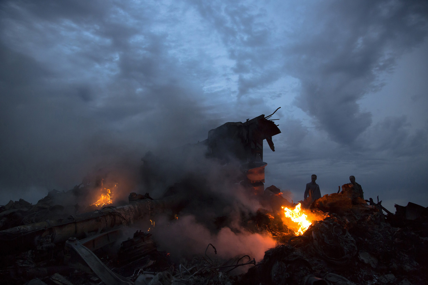 Jul. 17, 2014. People walk amongst the debris at the crash site of a passenger plane near the village of Grabovo, Ukraine, The passenger plane carrying 295 people was reported to have been shot down as it flew over the country. Both the government and the pro-Russia separatists fighting in the region denied any responsibility for downing the plane.