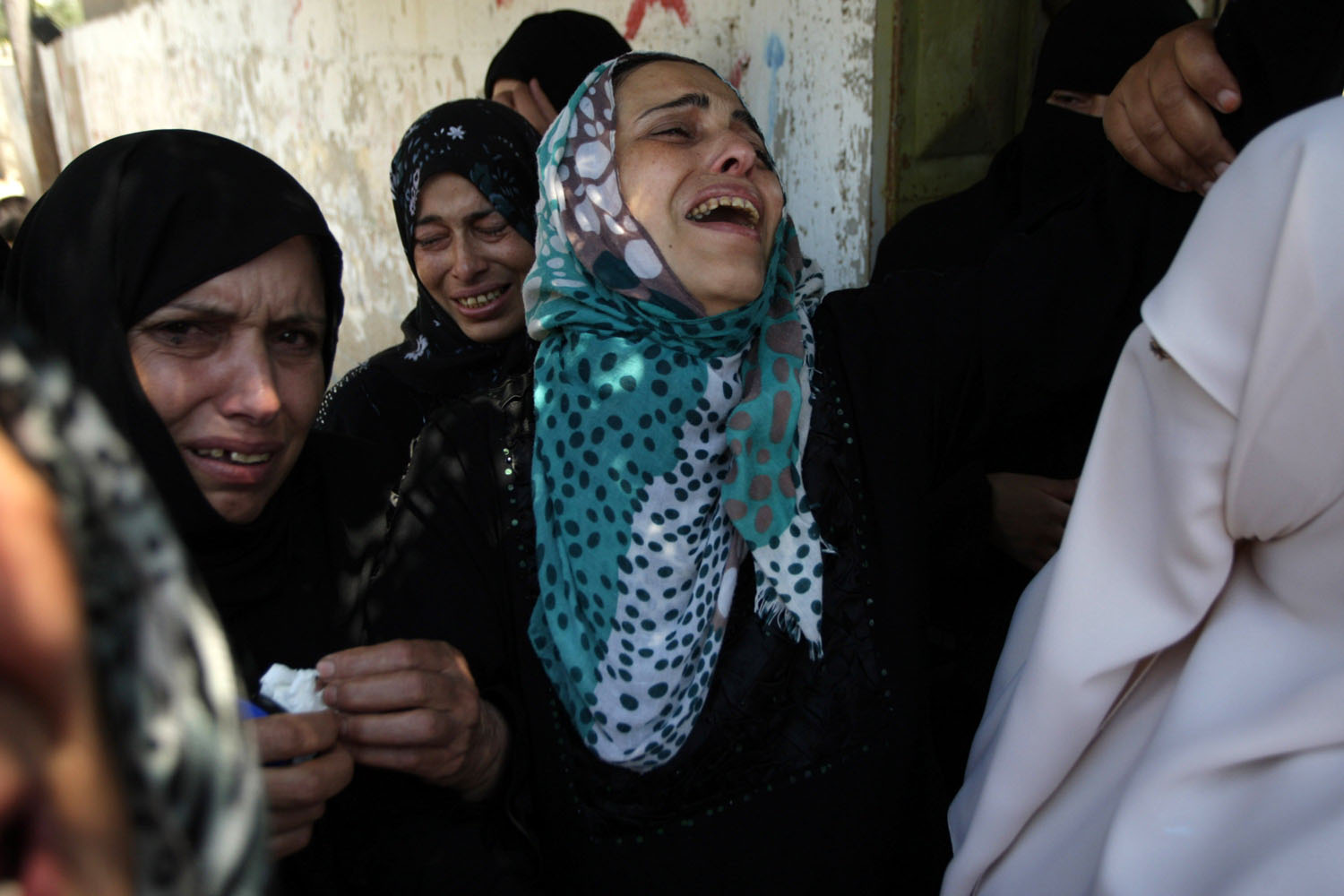 Jul. 9, 2014. Relatives and friends carry the bodies of the al-Kaware family as they mourn  during their funeral in Khan Yunis, in the Gaza Strip.The father and his six sons were all killed in an Israeli air strike that hit their home.