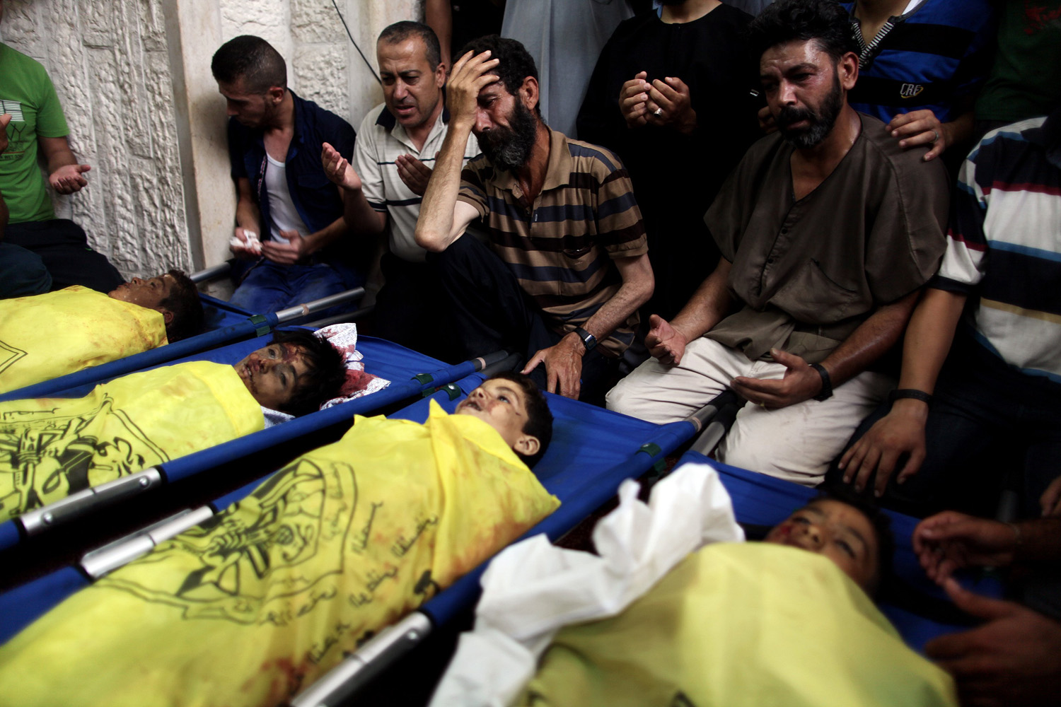 Jul. 16, 2014. Palestinians mourn over the body of boys from the Baker family, whom medics said was killed with three other children from the same family by a shell fired by an Israeli naval gunboat, in Gaza city.