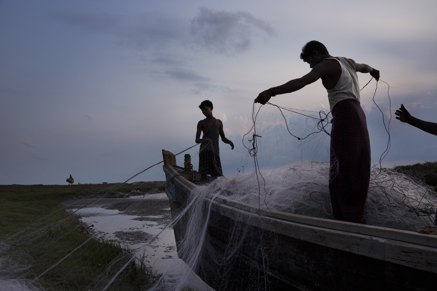 Fishermen tend their nets before going out into the Bay of Bengal to fish, one of the main sources of food and livelihood for the Rohingya.