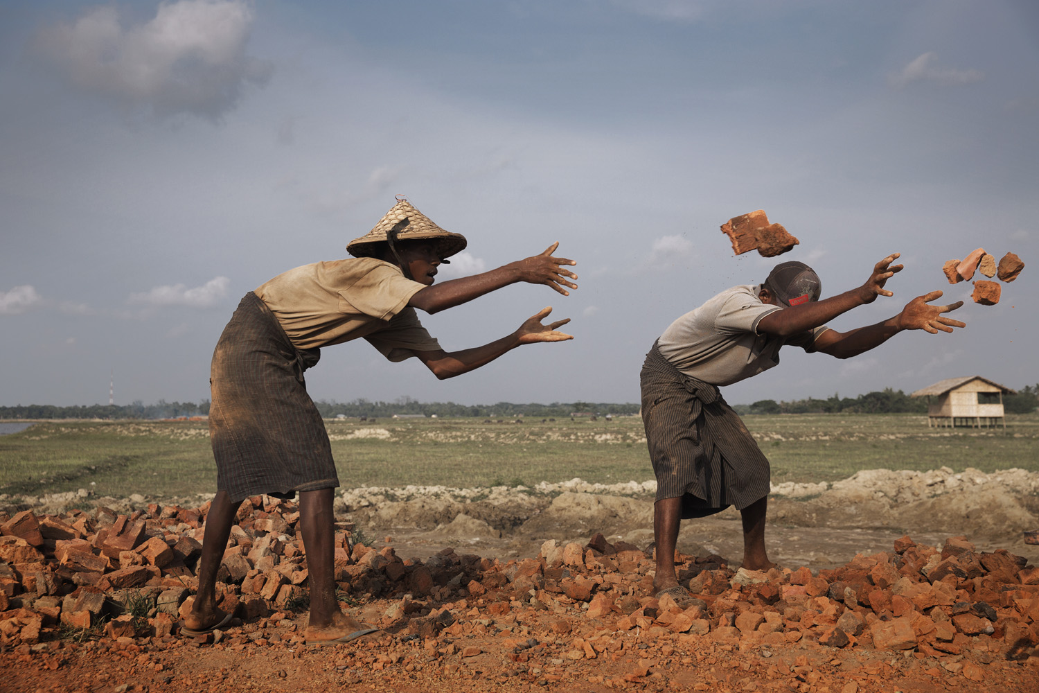 Workers at a brick kiln are seen tossing bricks.