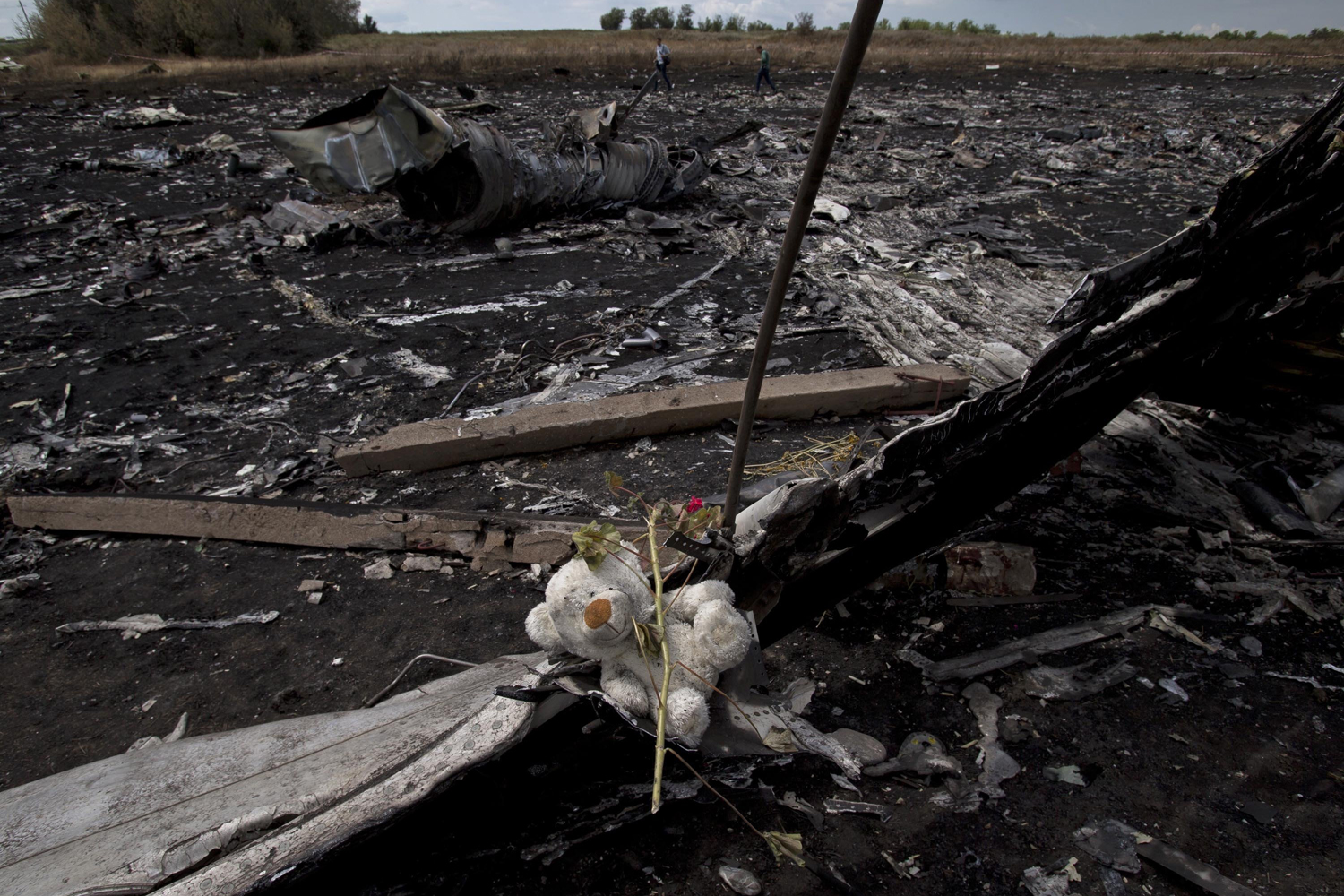 Jul. 22, 2014. A toy bear is placed on charred plane fuselage parts, as people walk through the crash site of Malaysia Airlines Flight 17 near the village of Hrabove, eastern Ukraine.