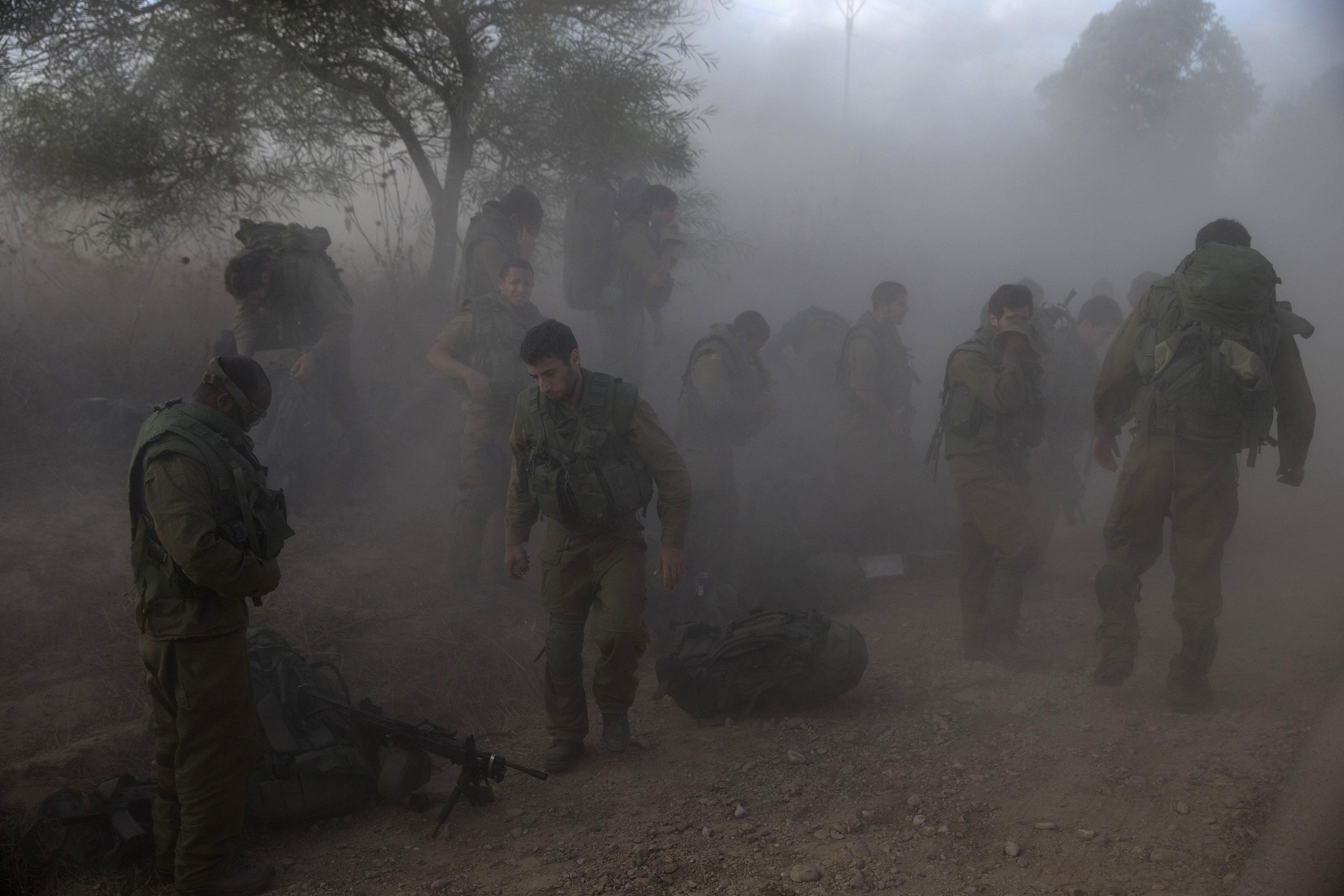 Israeli soldiers put on their gear on the side of a road across from the Gaza Strip on July 18, 2014.