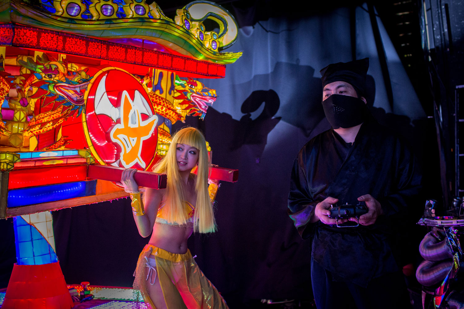 A stage hand dressed as a ninja controls a vehicle by remote control during a show at The Robot Restaurant on June 29, 2014 in Tokyo.