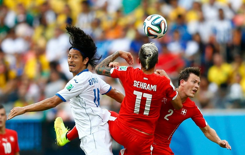 Roger Espinoza of Honduras fights for the ball with Switzerland's Valon Behrami and Stephan Lichtsteiner during their match at the Amazonia arena in Manaus, Brazil onJune 25, 2014.