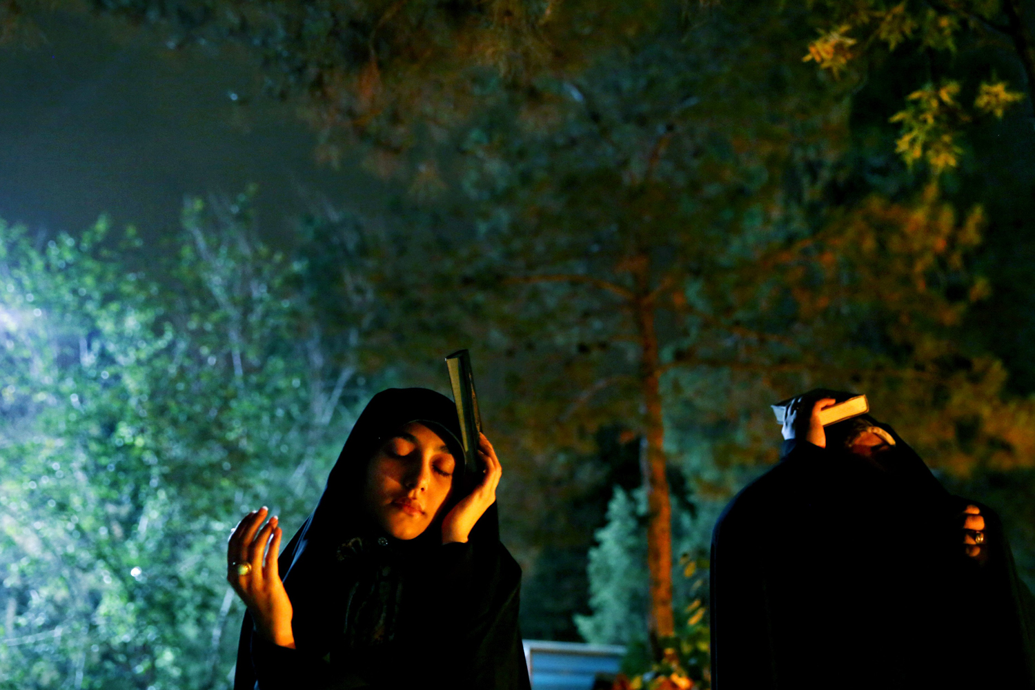 Jul. 19, 2014. Iranian Shiite Muslim women pray as they place the Quran, Islam's holy book, on their heads during a religious ceremony at the graves of soldiers who were killed during 1980-88 Iran-Iraq war, at the Behesht-e-Zahra cemetery, during the holy fasting month of Ramadan, just outside Tehran, Iran.