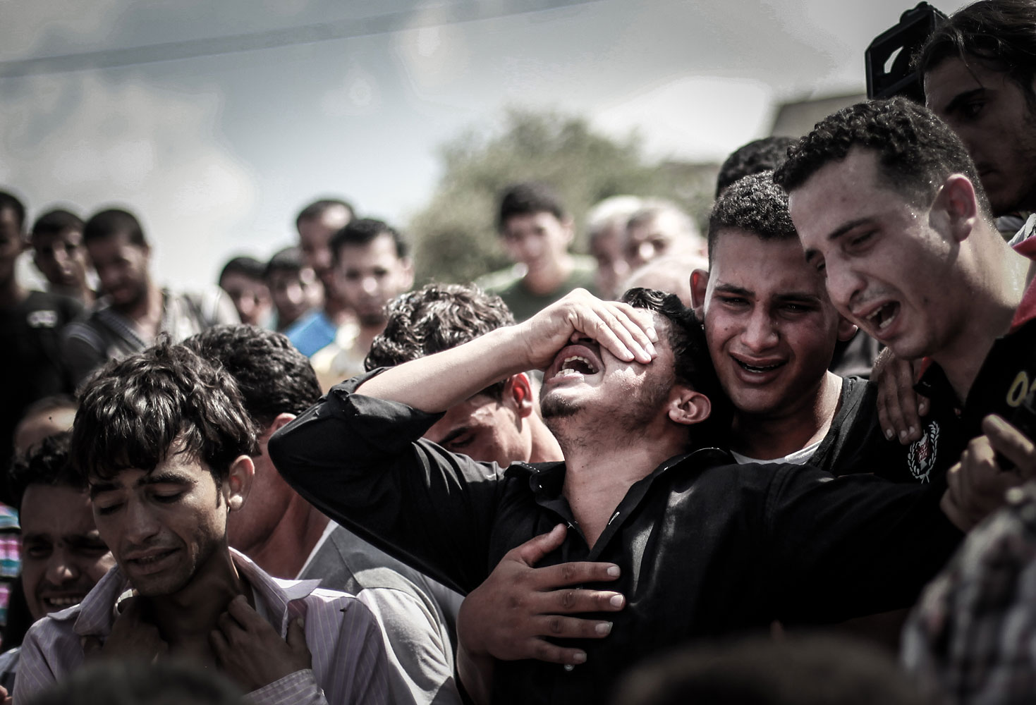 Palestinian relatives mourn during the funeral of eight members of the same family who were killed overnight in an Israeli strike on July 19, 2014 in Beit Lahia, north of the Gaza strip.
