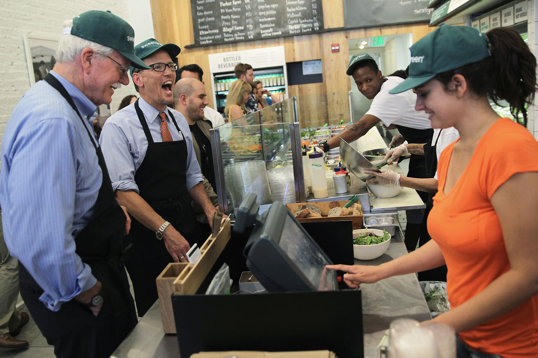 U.S. Labor Secretary Thomas Perez, second left, and Representative George Miller (D-CA) visit a Sweetgreen restaurant to discuss minimum wage, June 16, 2014 at Dupont Circle in Washington, DC.