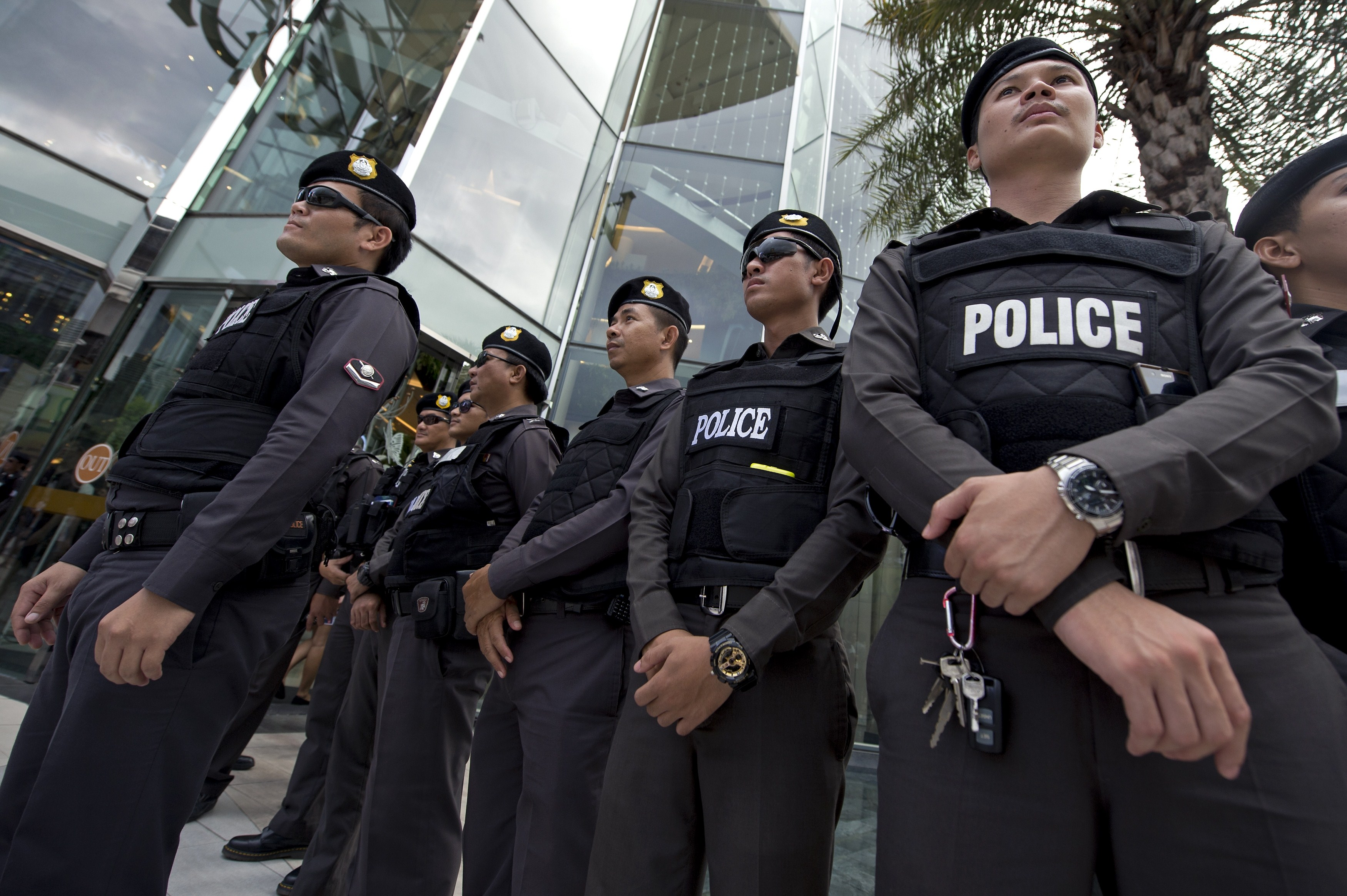 Thai policemen stand guard during a demonstration by an anticoup protester at a shopping mall in Bangkok on June 22, 2014.
