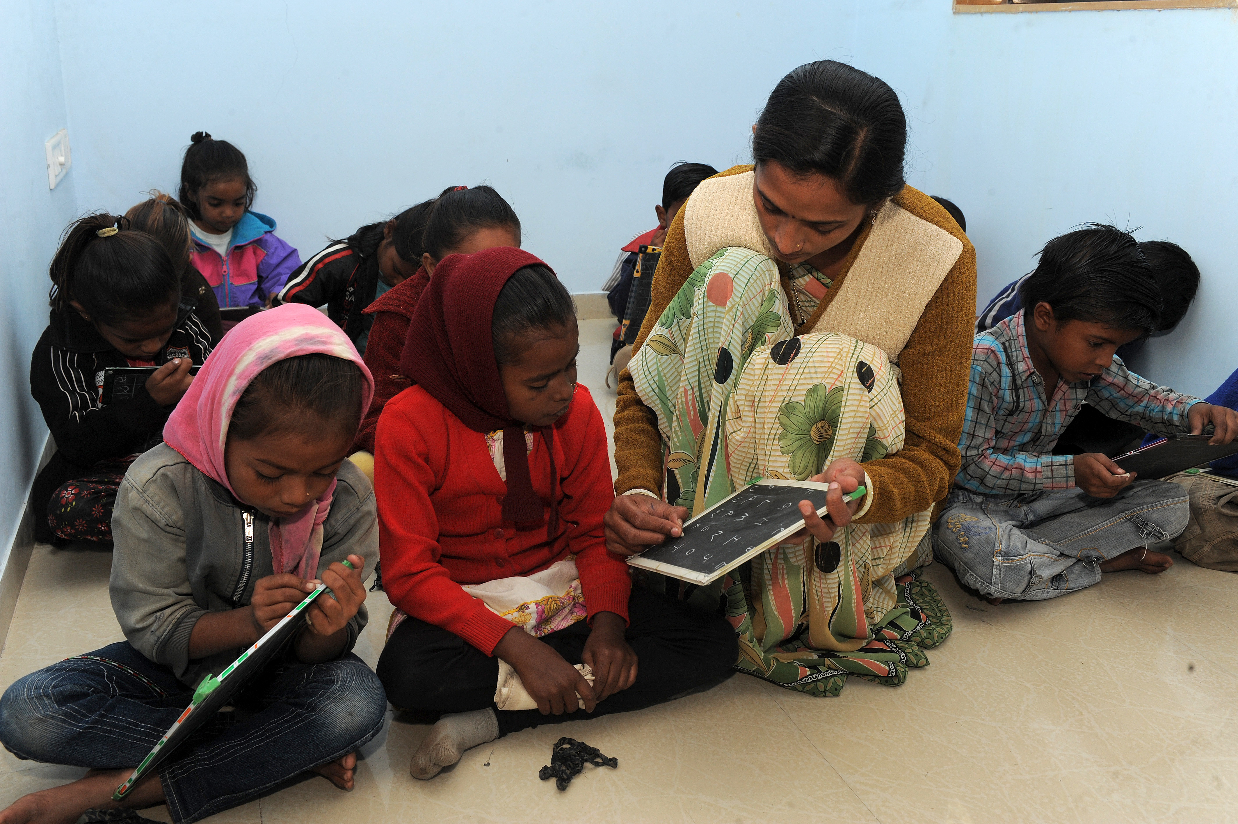 An Indian teacher assists underprivileged children during their lessons at Palodia village of Gandhinagar district, some 25 kms from Ahmedabad on November 21, 2013.