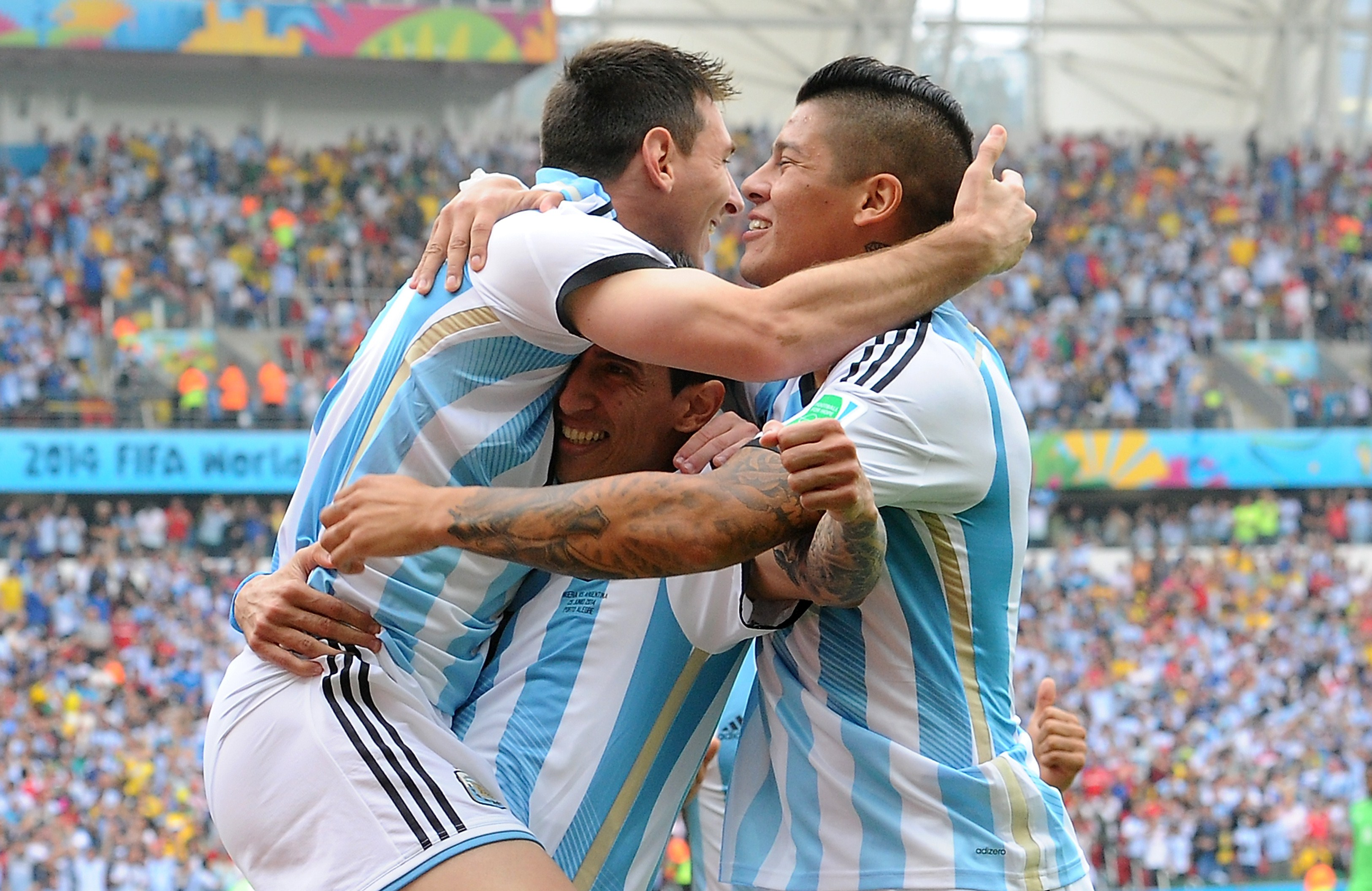 Argentina's forward and captain Lionel Messi (L) celebrates with teammates Argentina's midfielder Angel Di Maria (C) and Argentina's defender Marcos Rojo (R) after scoring during a match between Nigeria and Argentina on June 25, 2014,during the 2014 FIFA World Cup.