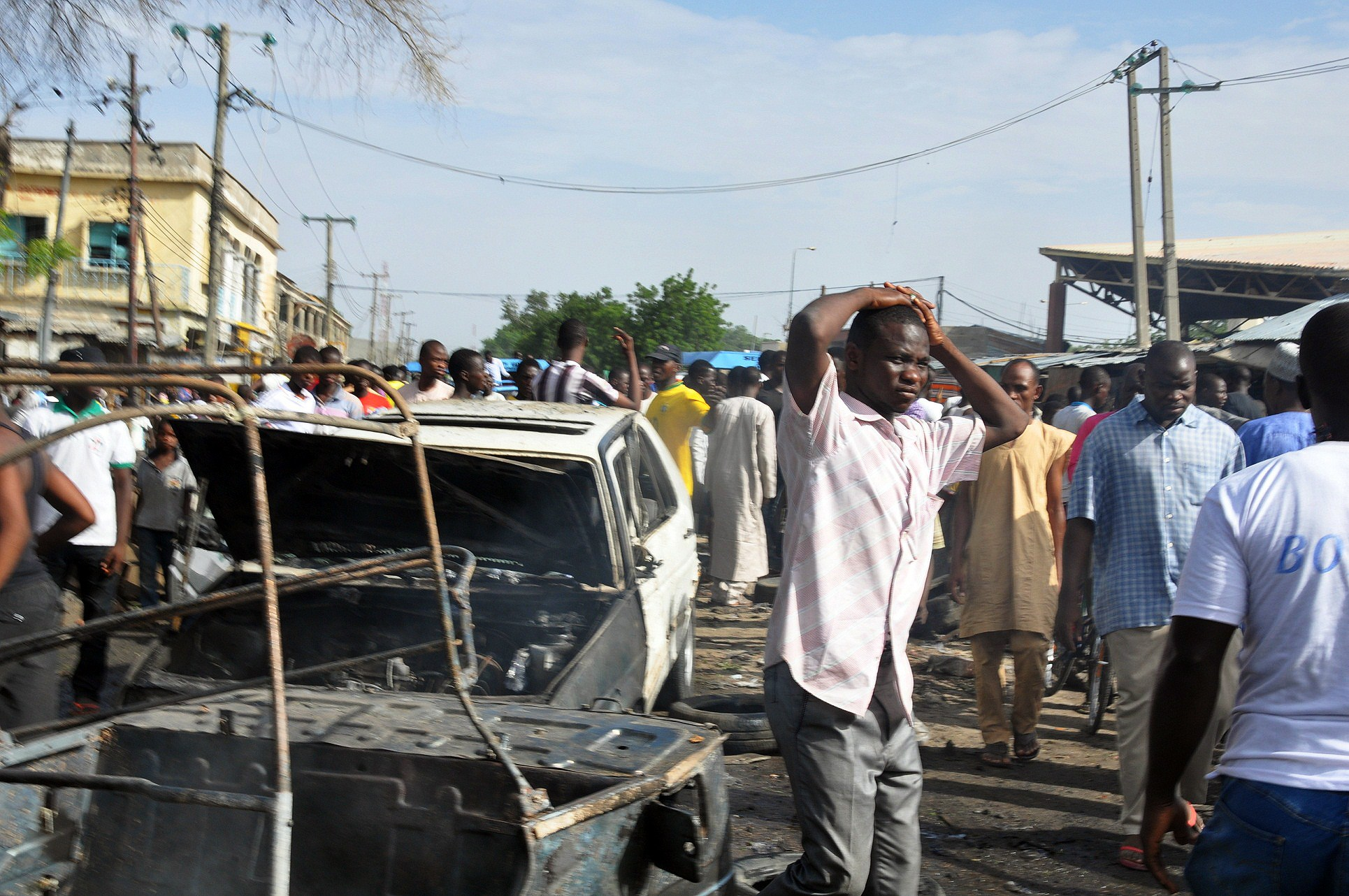 People gather near burned vehicles by the crowded Monday Market in Maiduguri, Nigeria, on July 1, 2014
