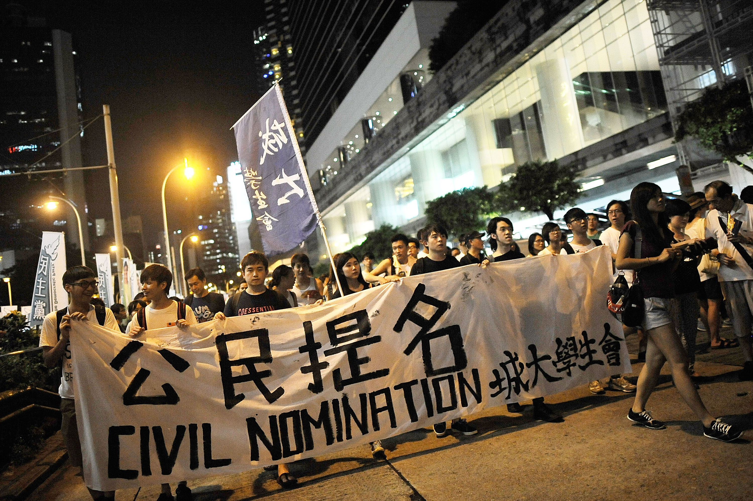 Protesters hold banners and flags as they march during the annual pro-democracy protest on July 1, 2014 in Hong Kong.