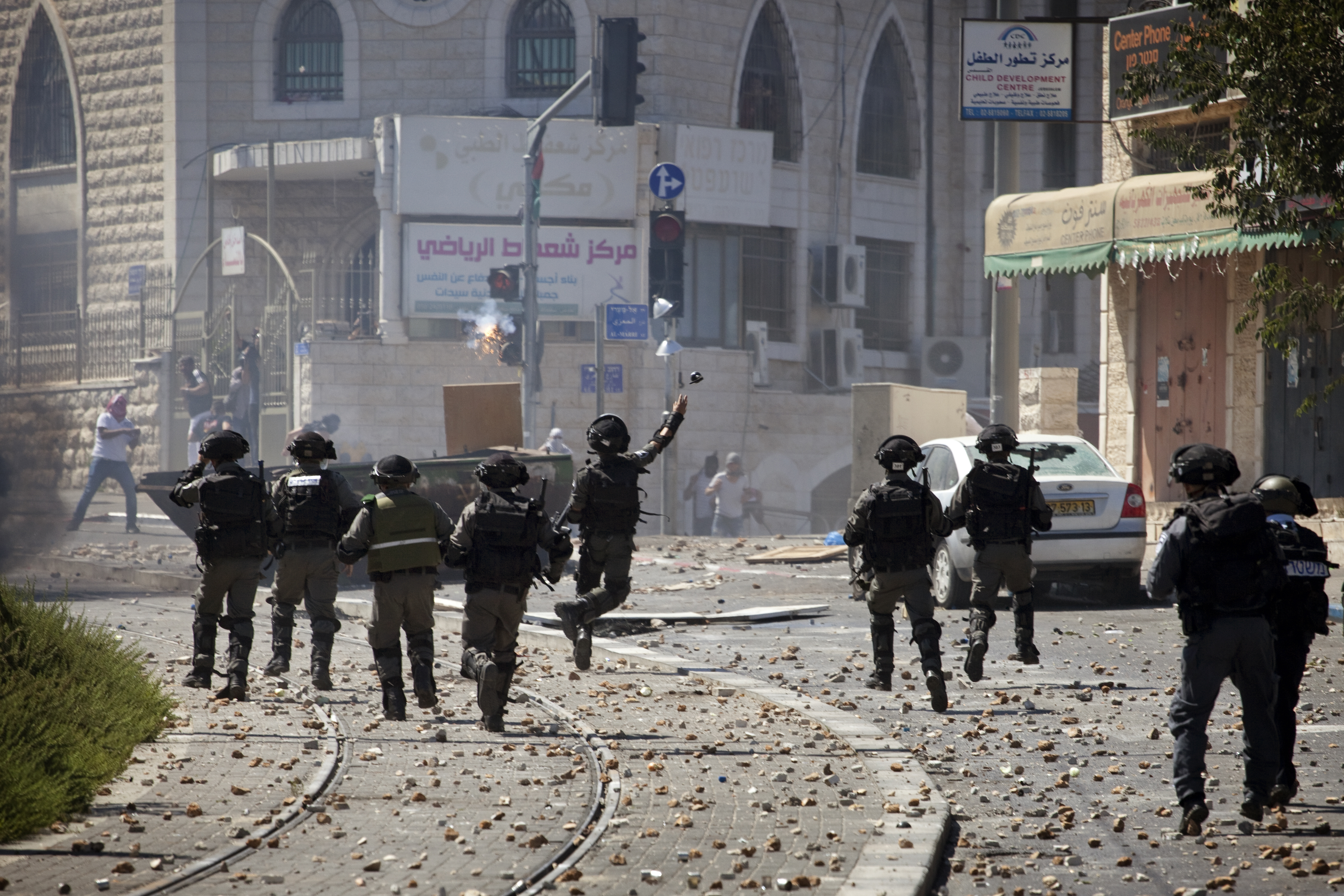 An Israeli soldier throws a grenade during clashes with Palestinians after a suspected kidnap and murder of a Palestinian teen