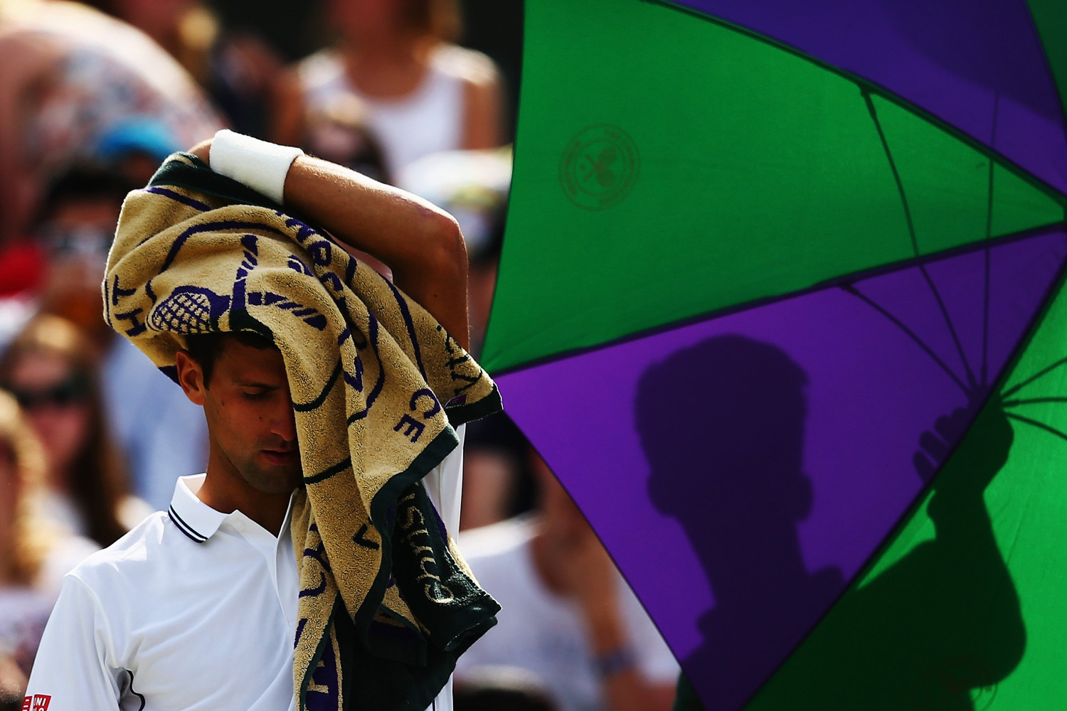 Jul. 2, 2014. Novak Djokovic of Serbia hides his face as he sits down during a change of end during his Gentlemen's Singles quarter-final match against Marin Cilic of Croatia on day nine of the Wimbledon Lawn Tennis Championships at the All England Lawn Tennis and Croquet Club  at Wimbledon in London, England.